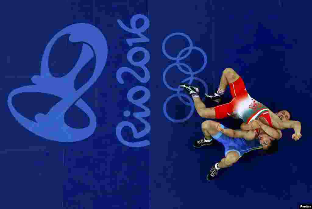 Hamid Mohammad Soryan of Iran and Almat Kebispayev of Kazakhstan compete in Greco-Roman wrestling in the 59-kilogram weight class.