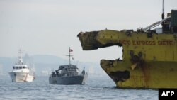 """A Philippine Coast Guard ship (left) and navy patrol boat (C) are anchored next to a damaged cargo ship on August 17, 2013 after it collided with the """"St. Thomas Aquinas"""" ferry the night before."""