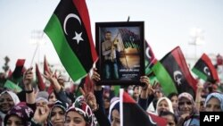 Women wave Libya's post-Qaddafi flag during celebrations in the streets of Tripoli after news of Muammar Qaddafi's capture and death on October 20.