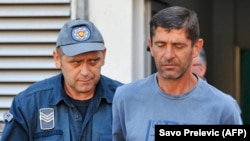 Vlado Zmajevic (right) is escorted by a police offier after being arrested in Niksic in August 2016.