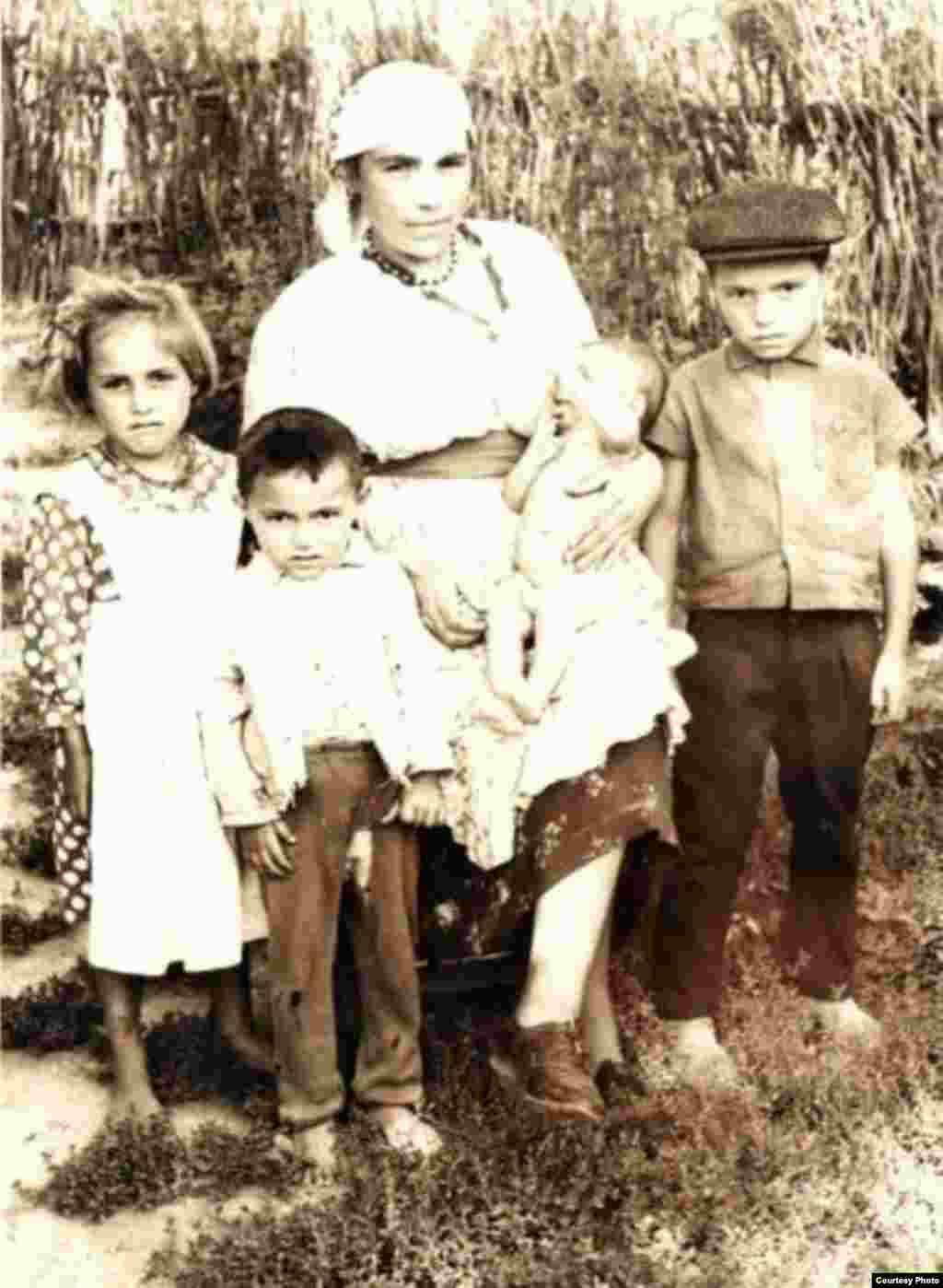 Mama lui Marin Alla în fața porții casei, alături de copii. Satul Ursari, circa 1950