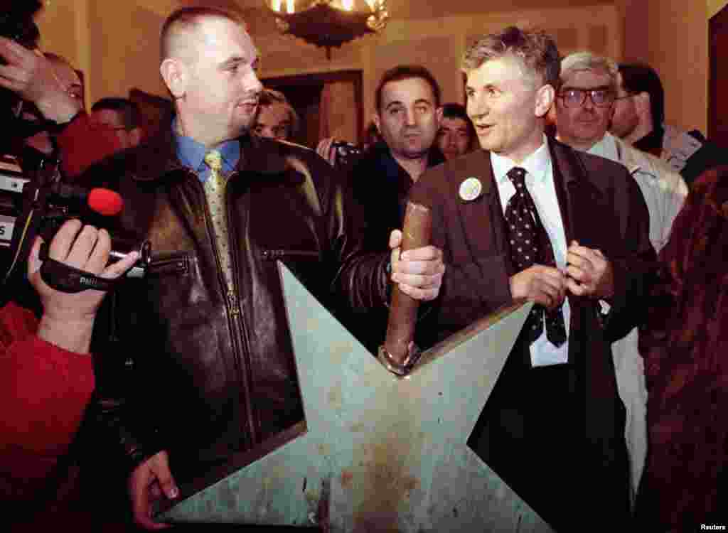 Djindjic took office as mayor of Belgrade in February 1997, becoming the city's first noncommunist mayor since World War II. Here, he stands next to a communist five-pointed star after it was removed from the Belgrade parliament building.