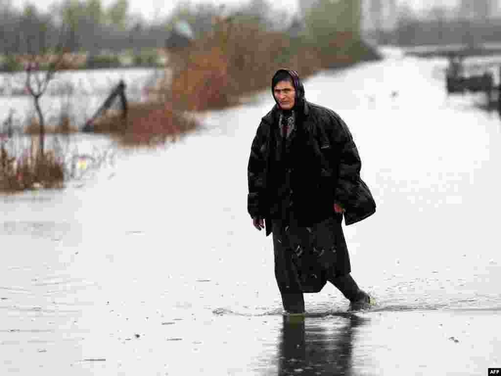 A woman walks near the Albanian village of Barbulloj, where flooding has forced dozens to flee their homes.