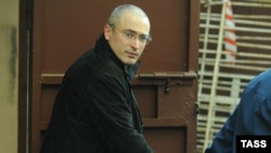 Handcuffed former Yukos head Mikhail Khodorkovsky is led away from Moscow's Khamovniki District Court