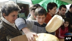 Refugees receiving bread at a camp for displaced persons outside Gori
