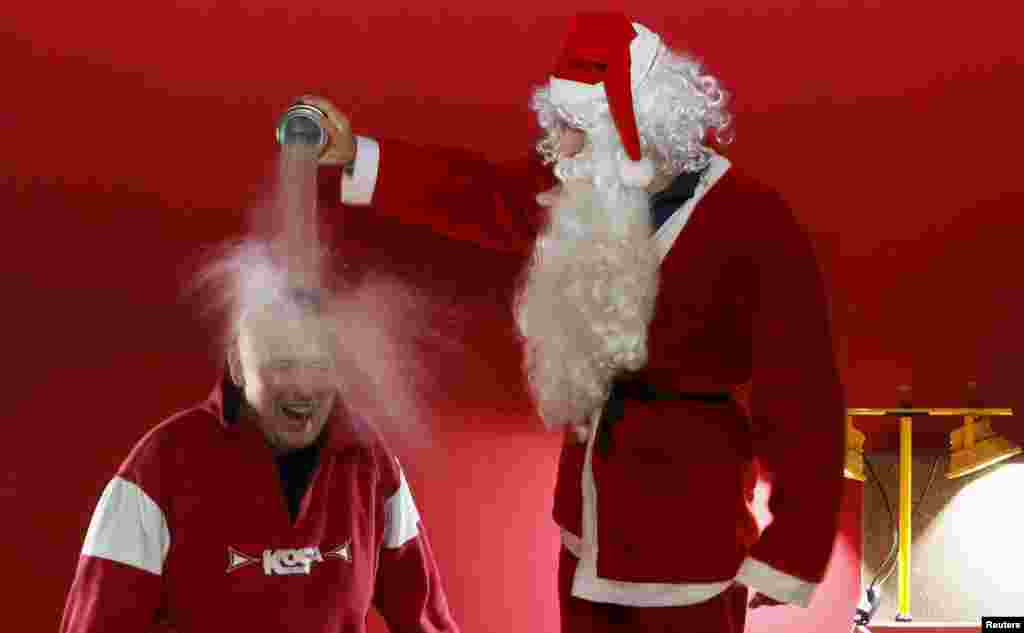 "Ivan Timofeenko, co-founder of ""Newton Park"", a private interactive Russian museum of science, dressed as Santa Claus, pours liquid nitrogen on the head of a visitor during a presentation on December 24. (Reuters/Ilya Naymushin)"