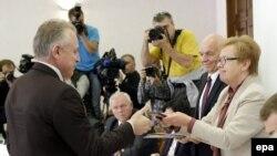 Բելառուս - Կենտրոնական ընտրական հանձնաժողովի նախագահ Լիդիա Երմոտշինան (աջից) նախագահական թեկնածուի նույնականացման քարտ է հանձնում Բելառուսի նախագահ Ալեքսանդր Լուկաշենկայի ներկայացուցիչ Միխայիլ Օրդային (ձախից), Մինսկ, 10-ը սեպտեմբերի, 2015թ․