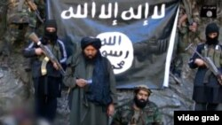 IMU leader Usmon Ghazi (second left) and his fighters are shown taking an oath of allegiance, in Arabic, to IS and its leader Abu Bakr al-Baghdadi.