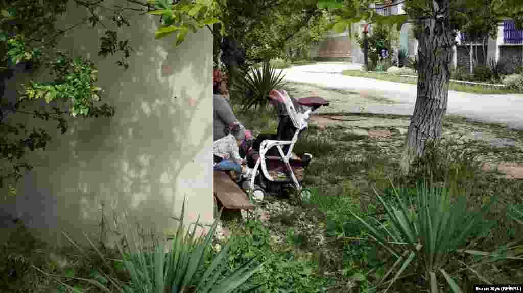 Бабуся з онукою відпочивають на лавці в приватному секторі