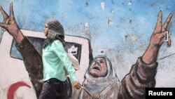 Palestine - A Palestinian woman walks past an anti-Israel mural in Gaza City, 02Sep2010