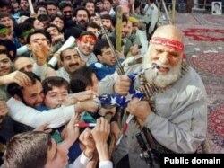يکی از واپسين عکس هايی که از حاجی بخشی در تجمعات بر جای مانده و او را در حال پاره کردن پرچم آمریکا با چنگ و دندان نشان می دهد