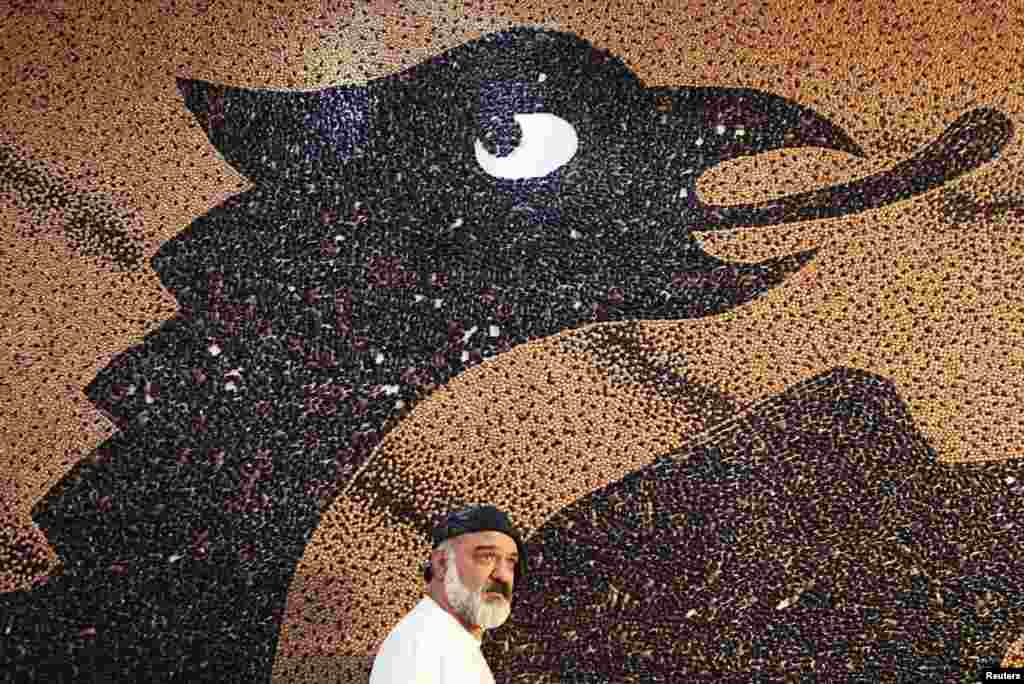 Albanian artist Saimir Strati appears in front of his mosaic of the Albanian flag at the Hotel Prishtina. The 65-square-meter mosaic, made of 1.35 million beans, earned Strati his seventh Guinness world record.