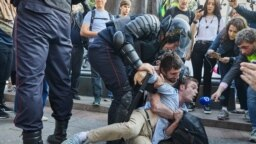 RUSSIA -- Timur Olevskiy, a TV anchor for Current Time TV, conducts an interview with a man as he is being detained by police at a rally to demand free municipal elections in Moscow, August 3, 2019