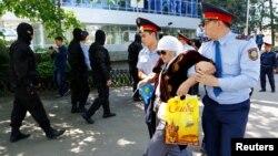 Полицейские задерживают женщину в день акции протеста против земельной реформы. Алматы, 21 мая 2016 года.