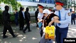 Полицейские производят задержание женщины в день протеста против земельной реформы. Алматы, 21 мая 2016 года.