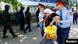 Полицейские задерживают женщину недалеко от площади Республики в Алматы. 21 мая 2016 года.