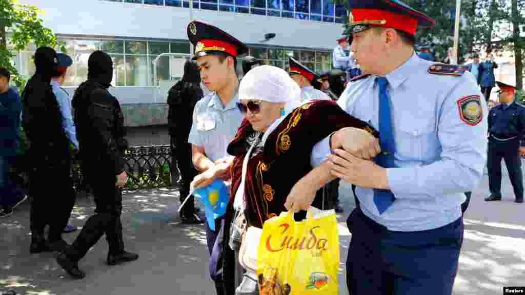 21 мамырда Алматыда түсірілген мына сурет кейін көпке танымал болды. Полиция қызметкерлері арнайы жасақ қоршаған көшеде ұсталған қарт әйелді қолтығынан ұстап, әкетіп барады.