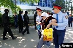 Полицейские ведут пожилую женщину, задержанную в день протеста в Алматы 21 мая 2016 года.