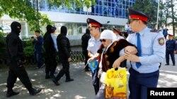 Полиция қарт адамды ұстап әкетіп барады. Алматы, 21 мамыр 2016 жыл. (Көрнекі сурет)