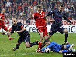 """""""Бавария"""" ойыншысы Томас Мюллер (ортада) лиондық футболшылар Крис, Антони Ревейер мен қақпашы Уго Льориске қарсы. Мюнхен, 21 сәуір 2010 жыл. (Көрнекі сурет)"""