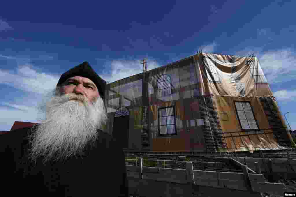 "Archpriest Georgy Yefimov poses in front of the tarp-covered frame of a new church his community is building in Sochi. His community of ""Old Believers"", who follow Russian Orthodox traditions dating from before reforms in the 17th century, lost their church to make way for the construction of the Olympic site. Efimov said getting building materials into the area had been nearly impossible while the Olympic construction wore on. (Reuters/Eric Gaillard)"