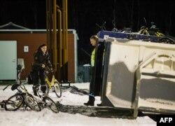 Норвежский полицейский выкидывает в мусорный контейнер велосипеды, которые используют обычно беженцы, чтобы проехать на территорию Норвегии из России. Стурскуг, 12 ноября 2015 года.