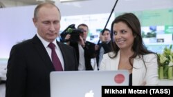Russia -- President Vladimir Putin and Russia Today (RT) editor-in-chief Margarita Simonyan attend an exhibition marking the 10th anniversary of RT, December 10, 2015.