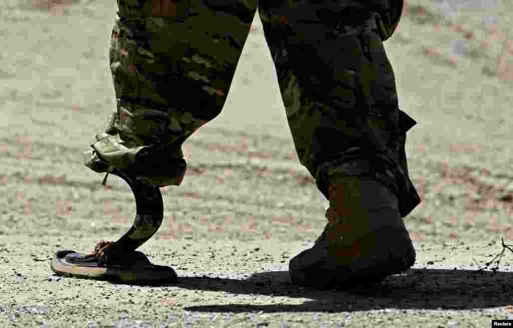 A NATO soldier walks with an artificial limb to board a Chinook helicopter after a security handover ceremony at a military academy outside Kabul. (Reuters/Omar Sobhani)