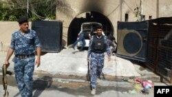 """عناصر أمن عراقيون يتفحصون آثار الهجوم على مقر جريدة """"المستقبل العراقي"""" في بغداد"""