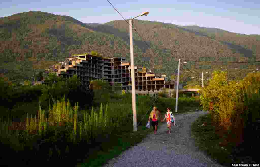 A Russian father and daughter walking to the beach at Gagra. An abandoned building site is in the background.