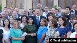 Президент Ильхам Алиев в окружении журналистов, получивших квартиры в новом доме, построенном для них