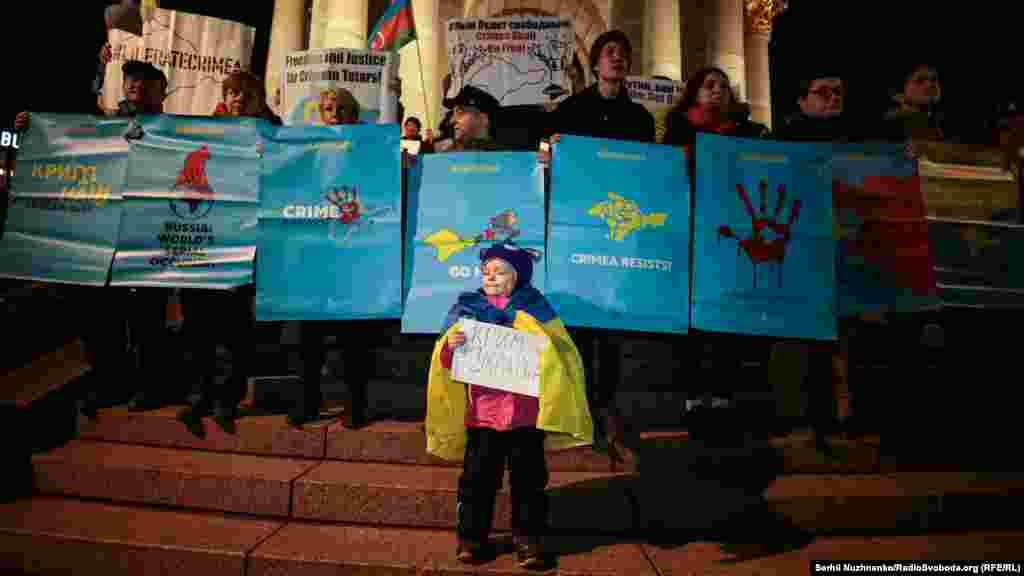 Активисты выстроились у Монумента Независимости Украины на одноименной площади в Киеве с плакатами, на которых были написаны требования к России прекратить оккупацию Крыма