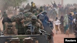 French troops aboard armored vehicles are greeted as they arrive in Timbuktu on January 28, after the Islamist rebels fled the city.