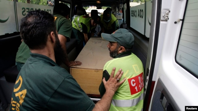 Hospital staff and rescue workers move the body of one of the 10 foreign tourists killed by gunmen near the Nanga Parbat peak in northern Pakistan.