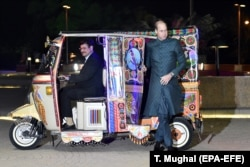 "Prince William steps out of a brightly decorated ""tuk-tuk"" on his arrival to a gathering in Islamabad, the Pakistani capital."
