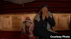 Тарбагатайлык кыргыз аял темир комуз кагууда.