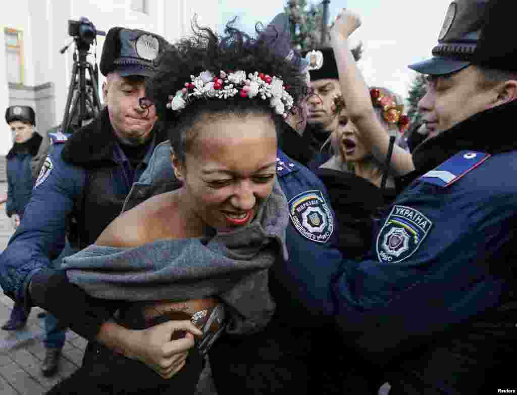 Ukrainian police detain activists of the women's rights group Femen as they protest against homophobia outside the parliament building in Kyiv on November 12. (Reuters/Gleb Garanich)