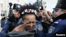 Украиналық полиция қызметкерлері наразылық акциясына шыққан Femen әйелдер қозғалысы белсенділерін ұстап жатыр. Киев, 12 қараша 2015 жыл.