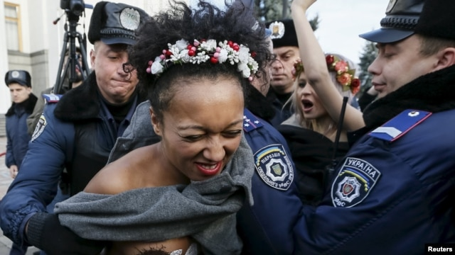Ukrainian police detain activists of the women's rights group Femen as they protest against homophobia outside the parliament building in Kyiv on November 12.