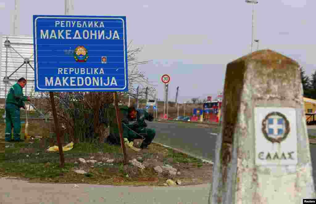 """Punëtorët duke pastruar zonën afër kufirit mes Maqedonisë së Veriut dhe Greqisë, afër Gjevgjelisë. Në fotografinë e bërë më 11 shkurt, tabela ende ka mbishkrimin """"Republika e Maqedonisë"""".REUTERS/Ognen Teofilovski"""