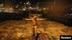 Участник Евромайдана проходит между шеренгами подразделений внутренних войск