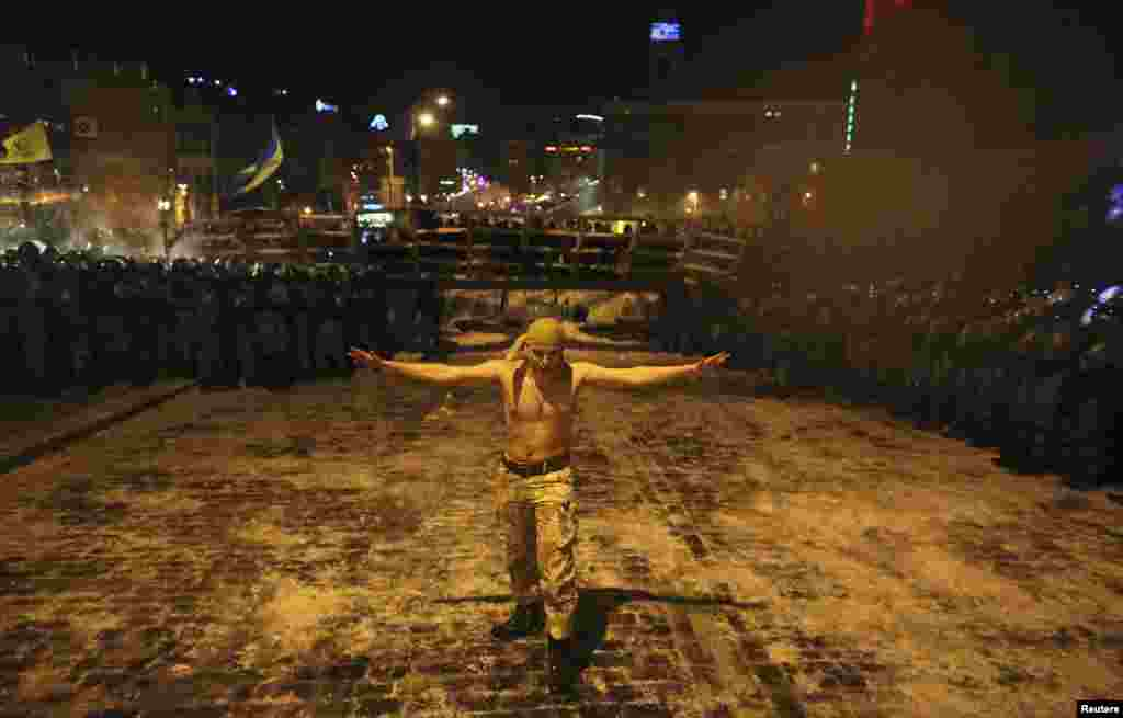 A Ukrainian antigovernment protester walks between a riot police line in Kyiv on December 11. (Reuters/Maksim Zveyev)