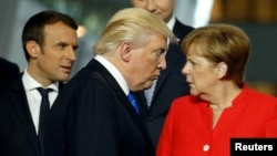 U.S. President Donald Trump (center) walks past French President Emmanuel Macron (left) and German Chancellor Angela Merkel (right) while getting into position for a group photo during a NATO summit in Brussels last May.