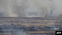 A photo taken from the Israeli-occupied Golan Heights shows smoke billowing from the Syrian side of the border.