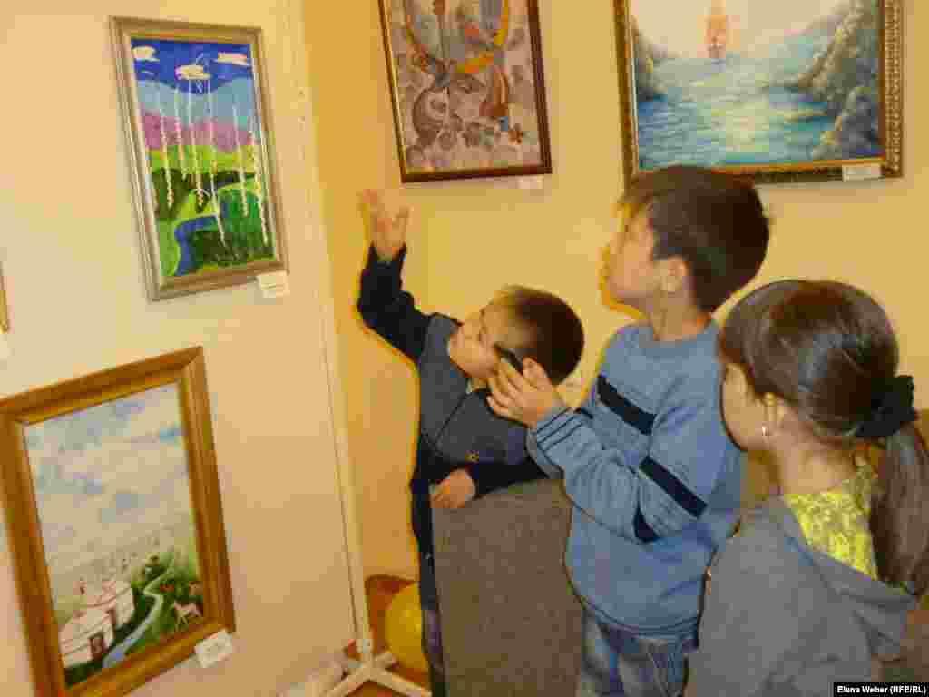 Дети рассматривают на выставке картины юных художников.
