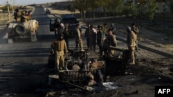 Afghan security forces investigate a site where vehicles were burned the previous night amid ongoing fighting against Taliban militants near the airport in Kunduz on October 1.
