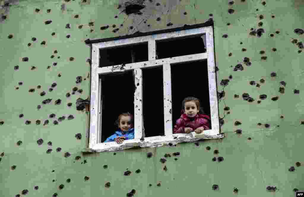 Children look out from a window of a bullet-scarred house in the Kurdish town of Silopi, in southeastern Turkey, near the border with Iraq. (AFP/Ilyas Akengin)