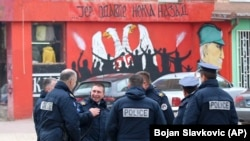 "Police officers stand by the graffiti that shows a Serbian coat of arms and silhouettes of people, reading: ""...because there's no turning back"" in the northern Serb-dominated part of the town of Mitrovica on November 23."