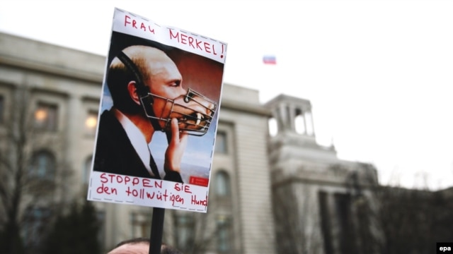 "A Ukrainian demonstrates with a poster depicting Russian President Vladimir Putin with a muzzle and text calling on German Chancellor Angela Merkel to ""stop the mad dog"" in front of the Russian embassy in Berlin on March 17."