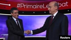 Французские политики Франсуа Фийон и Ален Жюппе жмут руки перед теледебатами. Париж, 24 ноября 2016 года.